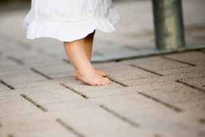 Little baby girl standing with barefoot